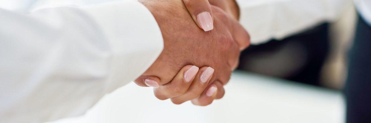 caucasian-businessman-shaking-hands-with-businessw-EUTRDAZ